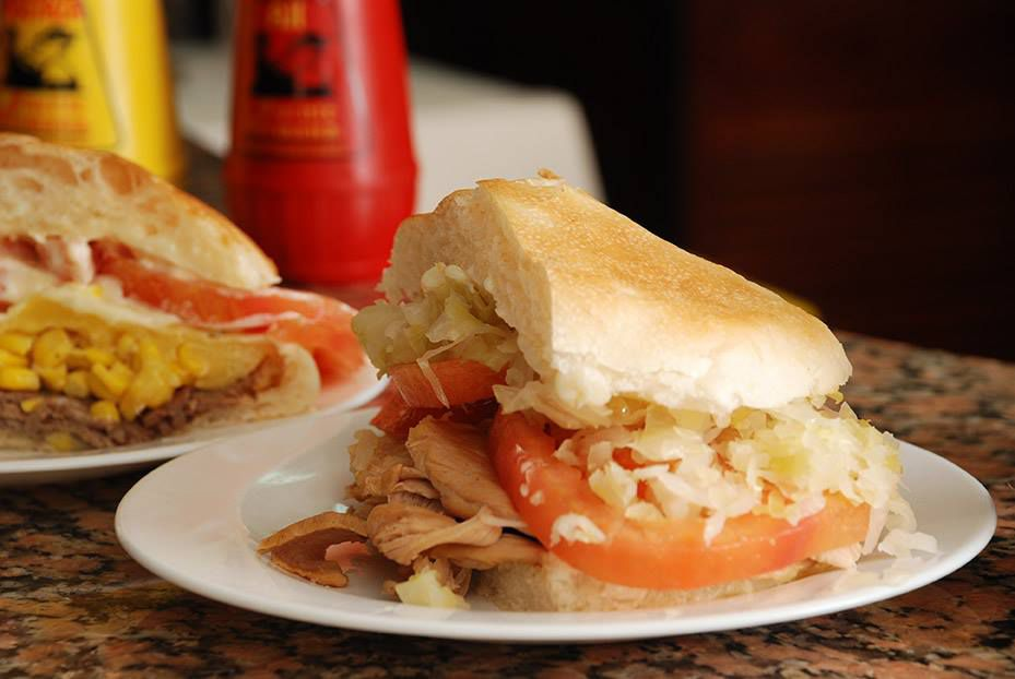Half a tall sandwich loaded with slices of beef, tomato and slaw on thick crusty bread, sitting on a counter beside another similar sandwich and bottles of condiments
