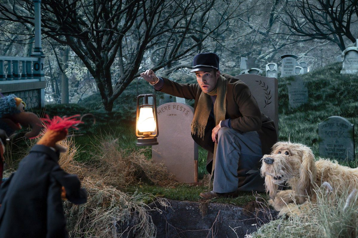 darren criss in a graveyard in muppets haunted mansion