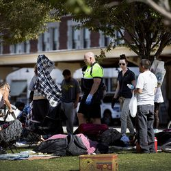Salt Lake City police officer Lyman Smith and Karla Bartholomew, a health scientist with the Salt Lake County Health Department, ask homeless people to remove their belongings from 500 West on Wednesday, Sept. 28, 2016.