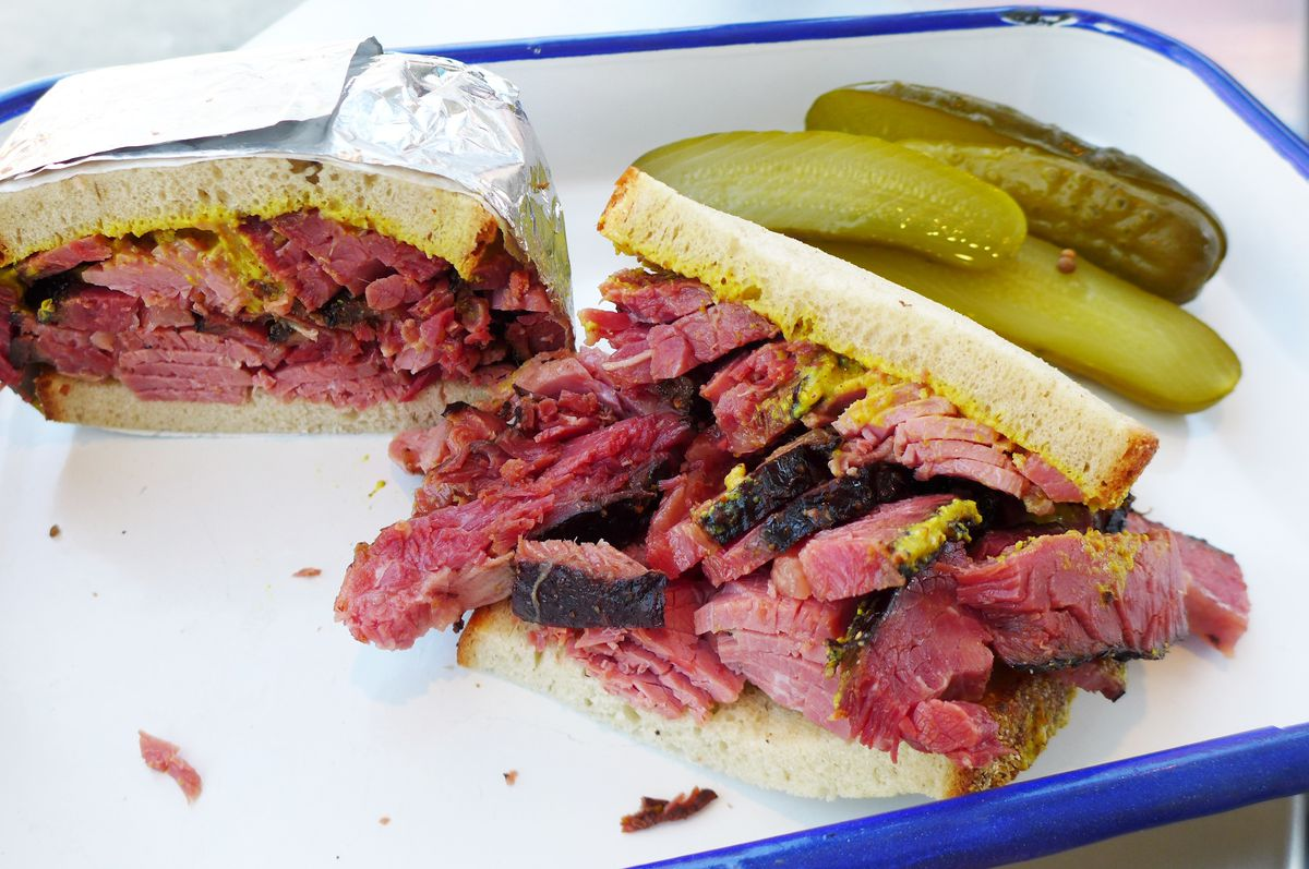 A jagged pastrami sandwich bursting with thick slices of deeply red pastrami, one half still wrapped in foil.