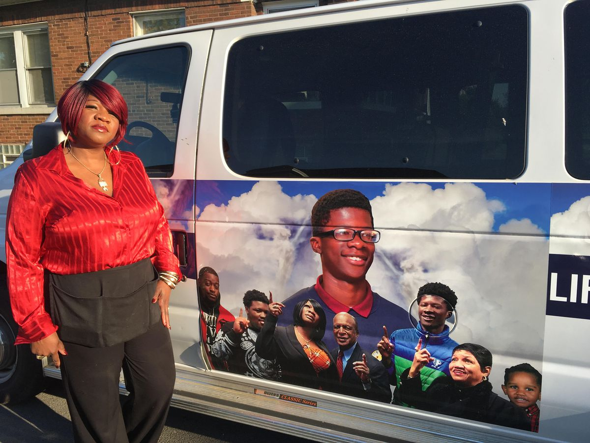 Delores Bailey stands next to a van emblazoned with photos of her murdered son, which she now uses to transport youth in her neighborhood to and from after-school events in the wake of her son's death.   Maudlyne Ihejirika/Sun-Times