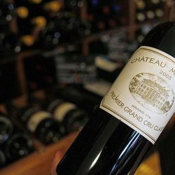 In this Sept. 20 2012, photo, a wine seller presents a 2005 bottle of Bordeaux wine Chateau Margaux at his shop in Paris. The United States wants to sell some of their wines in the European Union with a ''chateau'' label.  Next week, EU experts will look whether it should permitted with a fight among member states set for later this year, well after the wine harvest.