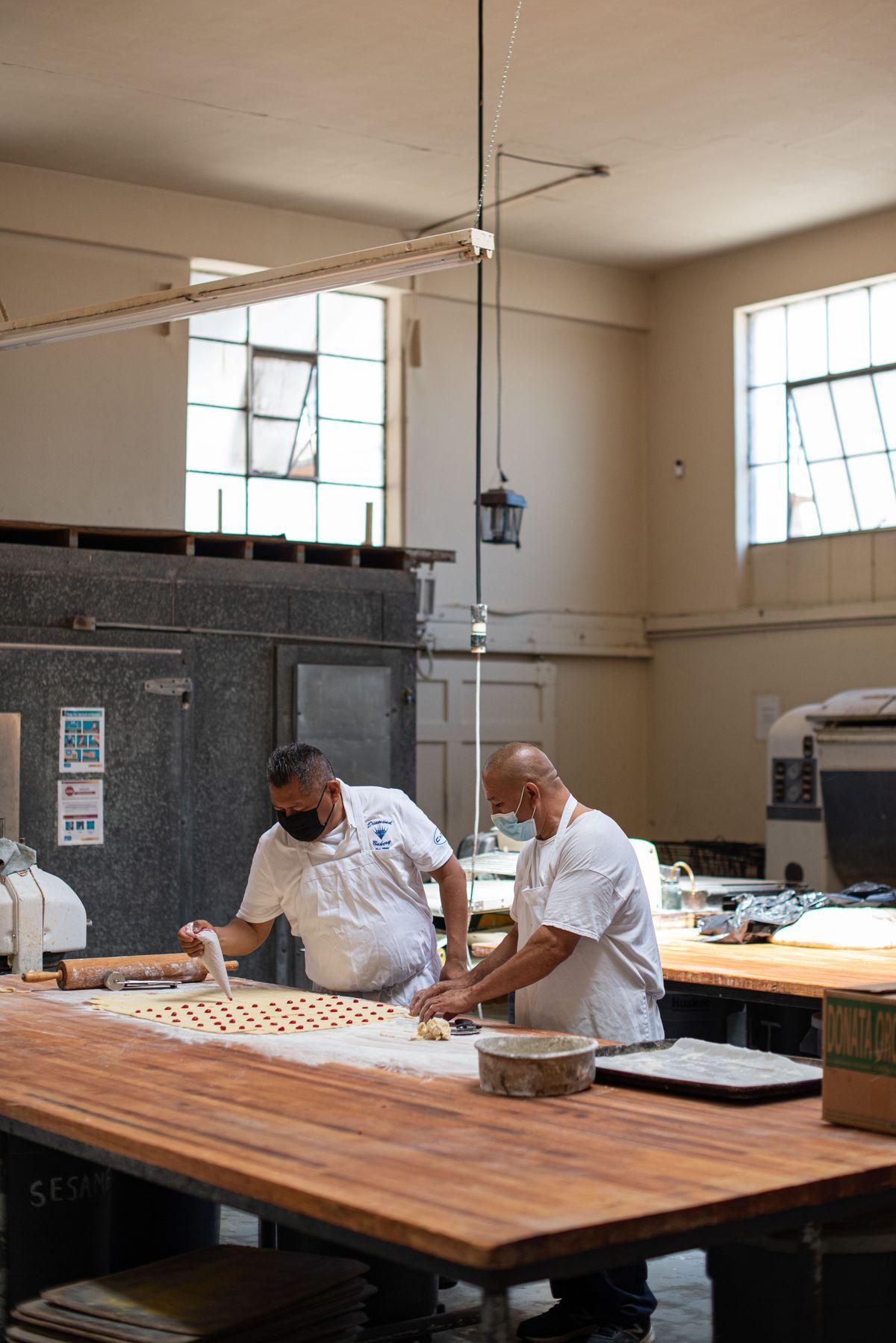 Hai công nhân chuẩn bị bánh ngọt Do Thái bên trong một tiệm bánh âm u, đổ bột nhuyễn vào bánh ngọt.
