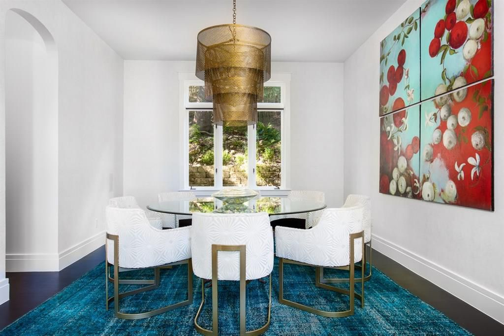 A small dining room with an arched doorway to the left, a glass table with rounded corners surrounded by six chairs, a large bronze modern telescoping chandelier above, a rug below, a window on one wall, and a large painting on the other.