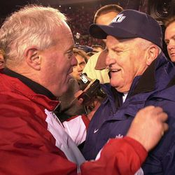 Brigham Young coach LaVell Edwards, right, is congratulated by Utah coach Ron McBride, left, at the end of the game against Utah, Friday, Nov. 24, 2000, in Salt Lake City. BYU won the game 34-27.  It was the final game of Edwards' 29-season career as BYU coach.