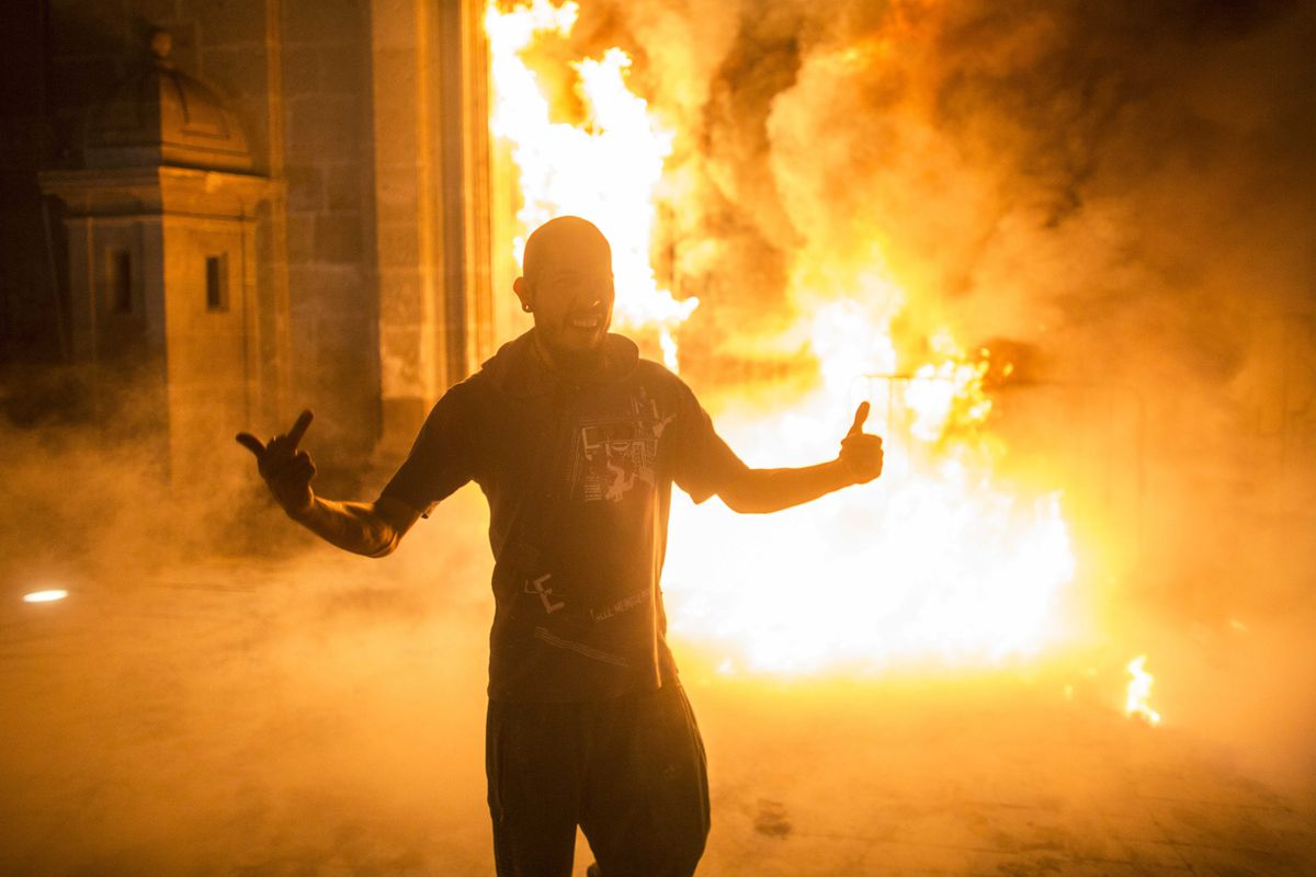 A protester in Mexico city in front of the burning Presidential Palace, which was set on fire during demonstrations on November 8