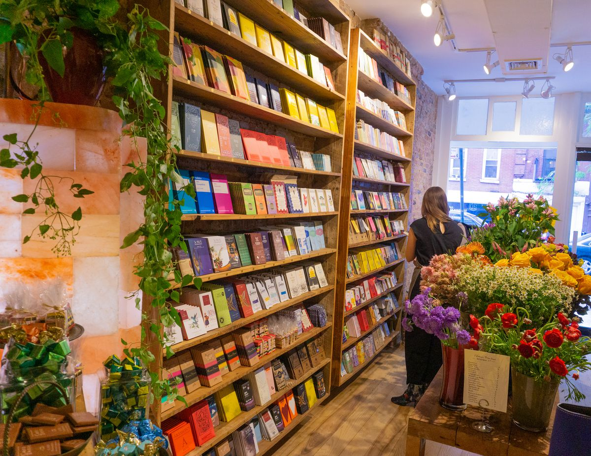 A wall with shelves lined with bars of chocolate flanked by a green plant on one side and vases of flowers on the other side.