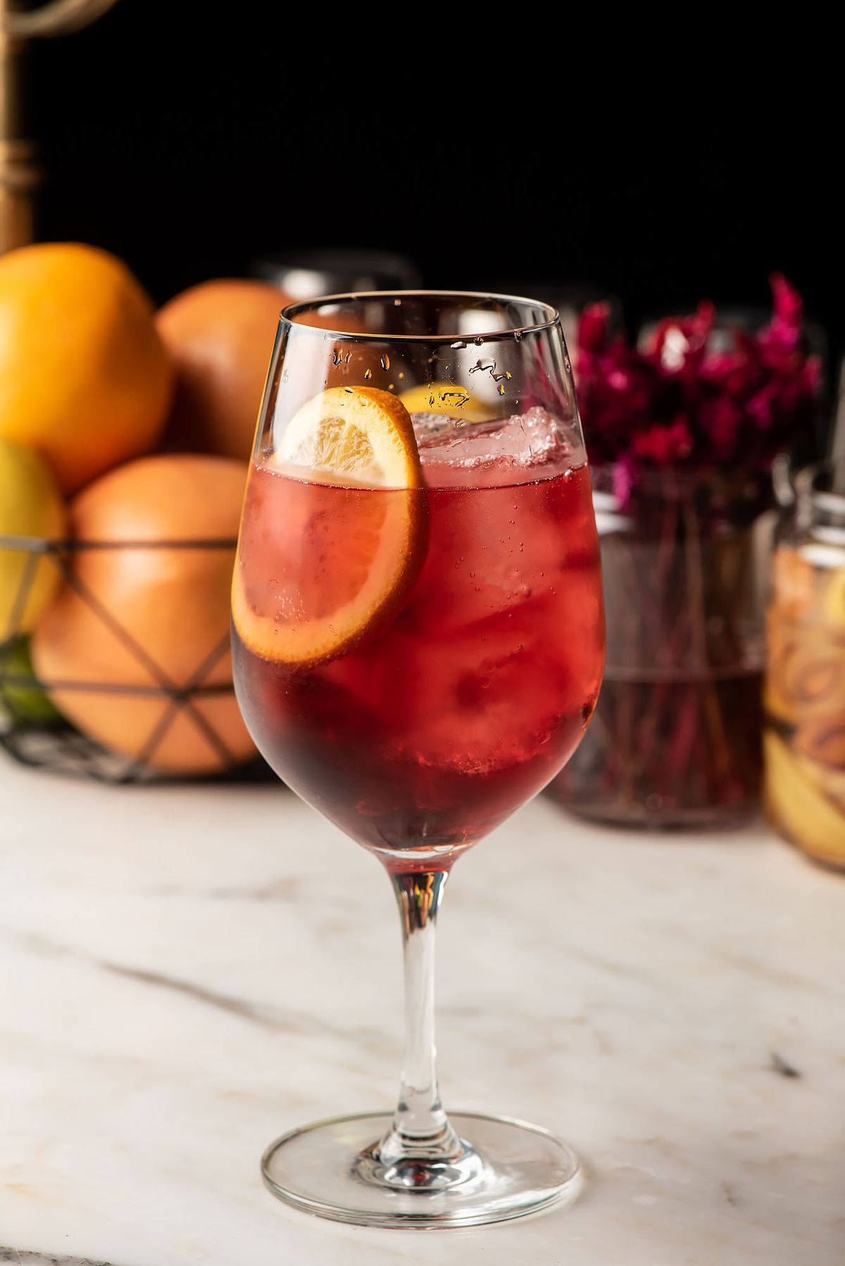 A deep red spritz with a slice of orange.