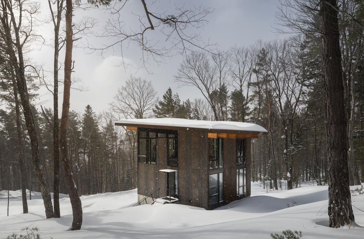 Wooden cabin in snowy woods.