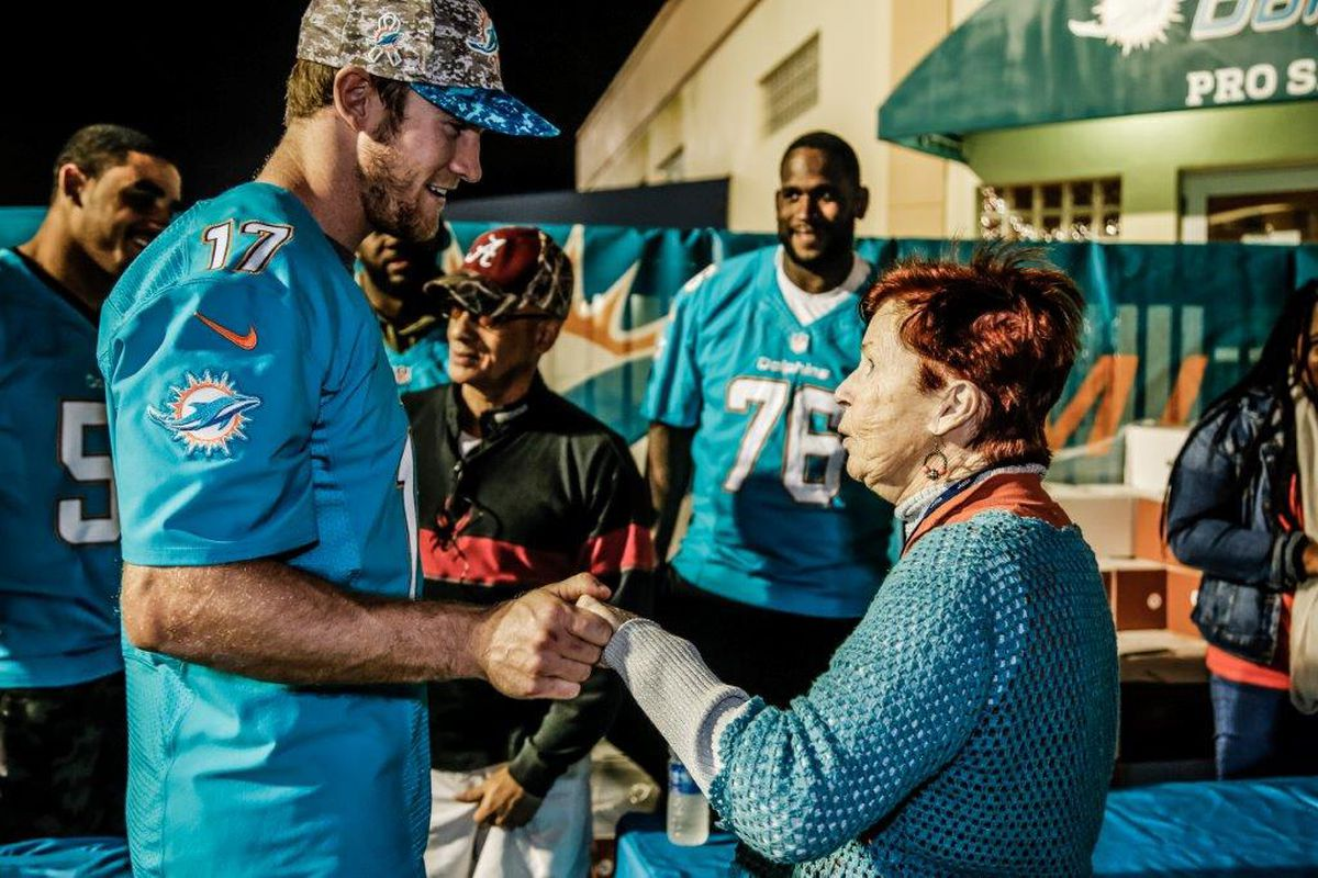 Ryan Tannehill (17) with Olivier Vernon (50) and Branden Albert (76) at Miami Dolphins Thanksgiving Meal Distribution