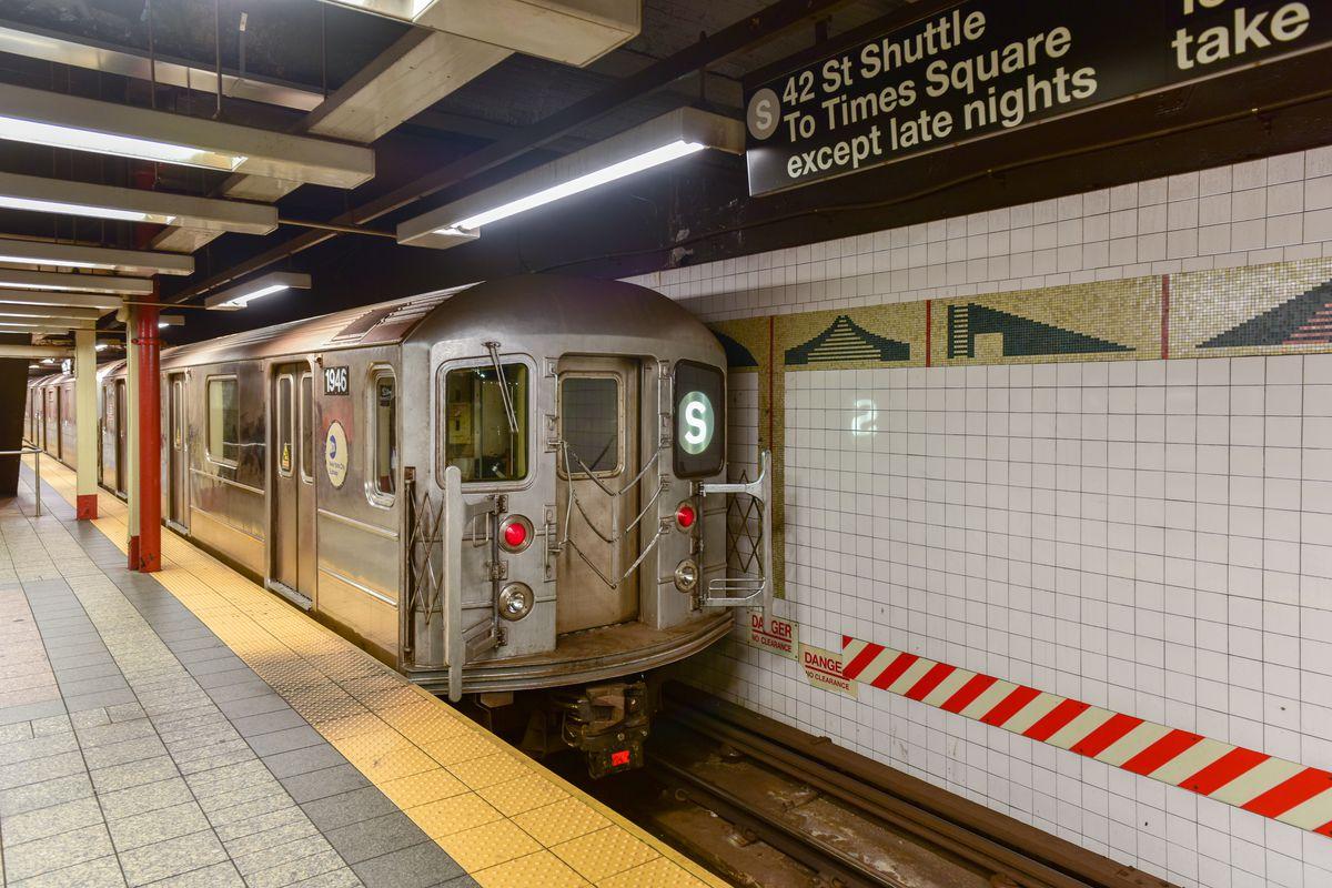 A shuttle subway train arrives at a platform.