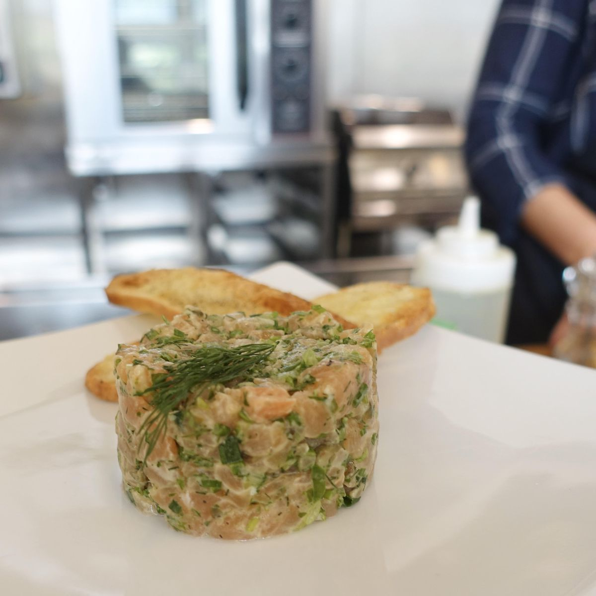 fish tartare on white plate with bread on the side