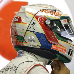 McLaren Formula One driver Lewis Hamilton of Britain puts his helmet on during the first practice session for the Singapore Formula One Grand Prix on the Marina Bay City Circuit in Singapore, Friday, Sept. 21, 2012.