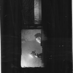 A technician from the crime laboratory searches for clues during a revisit by state's attorney's police to the apartment at 2337 W. Monroe where Fred Hampton and Mark Clark where slain Dec. 4, 1969. The picture was taken through a window from outside the building.