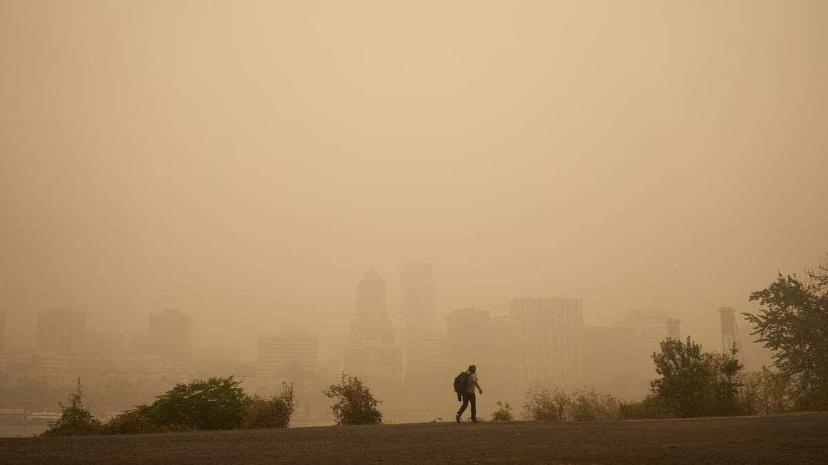 A man walks down the street in the Portland haze, with a few buildings in the background