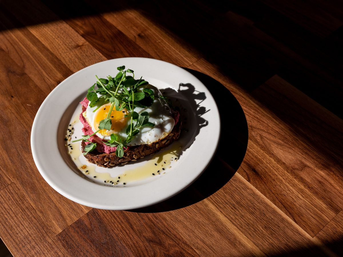 Toast topped with an egg and micro greens on a white plate on a wooden table