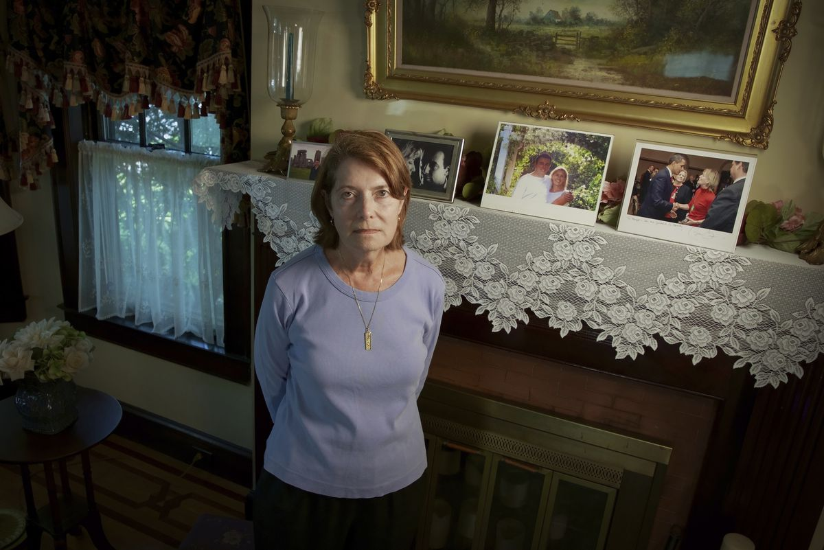 Margot Eckert stands by a display of pictures of her brother-in-law Sean Rooney and sister Beverly Eckert at her home in Springfield, Mass. Rooney was killed on 9/11 while working in his office in the South Tower. His wife Beverly Eckert died in a plane crash in 2009.