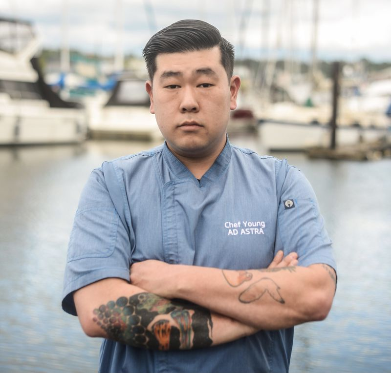 """Chef Young Cho with his arms folded in front of a marina, wearing a light blue shirt that has his name and the words """"Ad Astra"""" on it."""