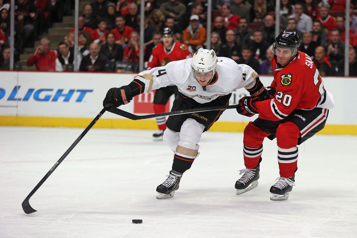 Cam Fowler and Brandon Saad battle for the puck.