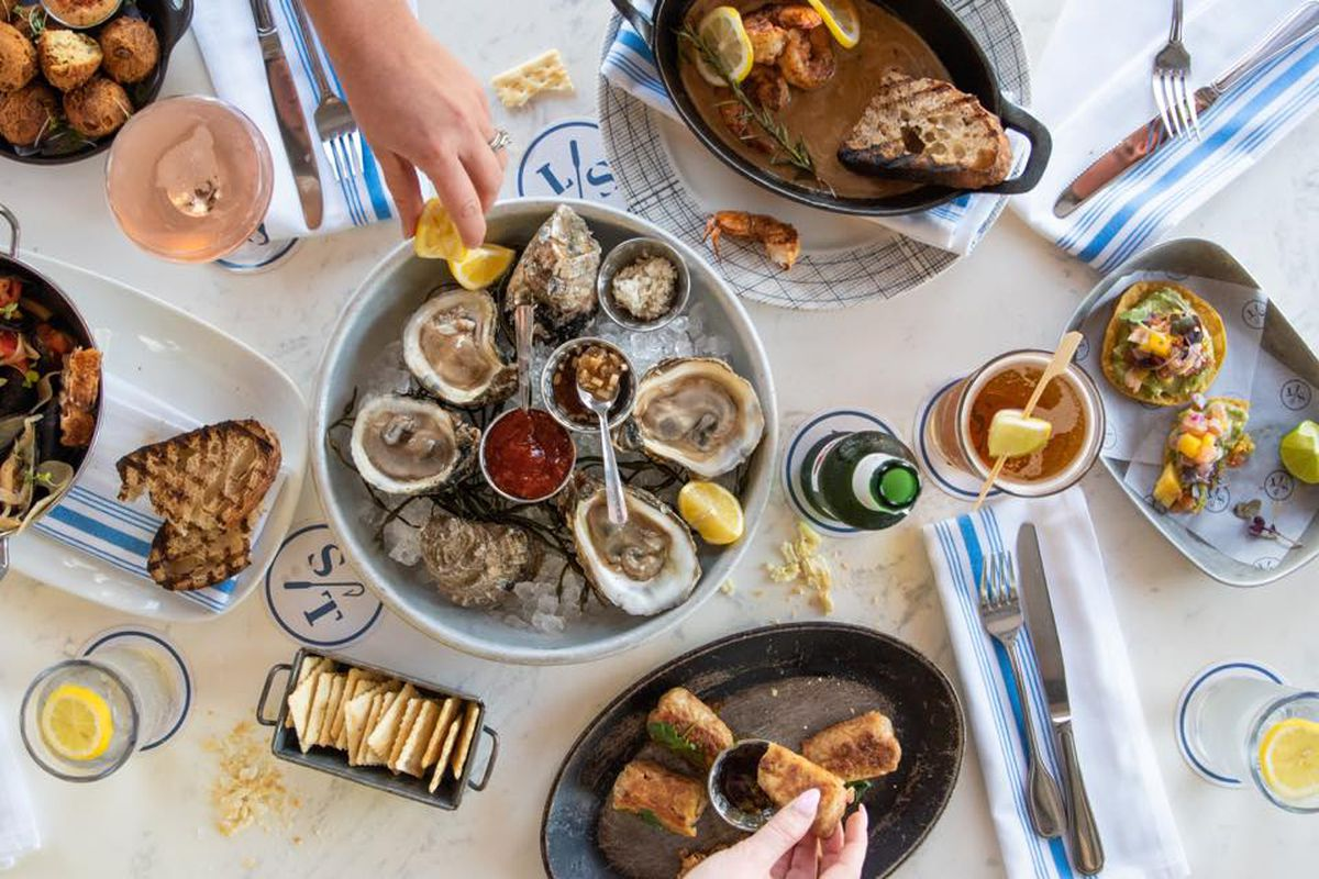 A table full of dishes like oysters, sandwiches, crackers, toast, etc.