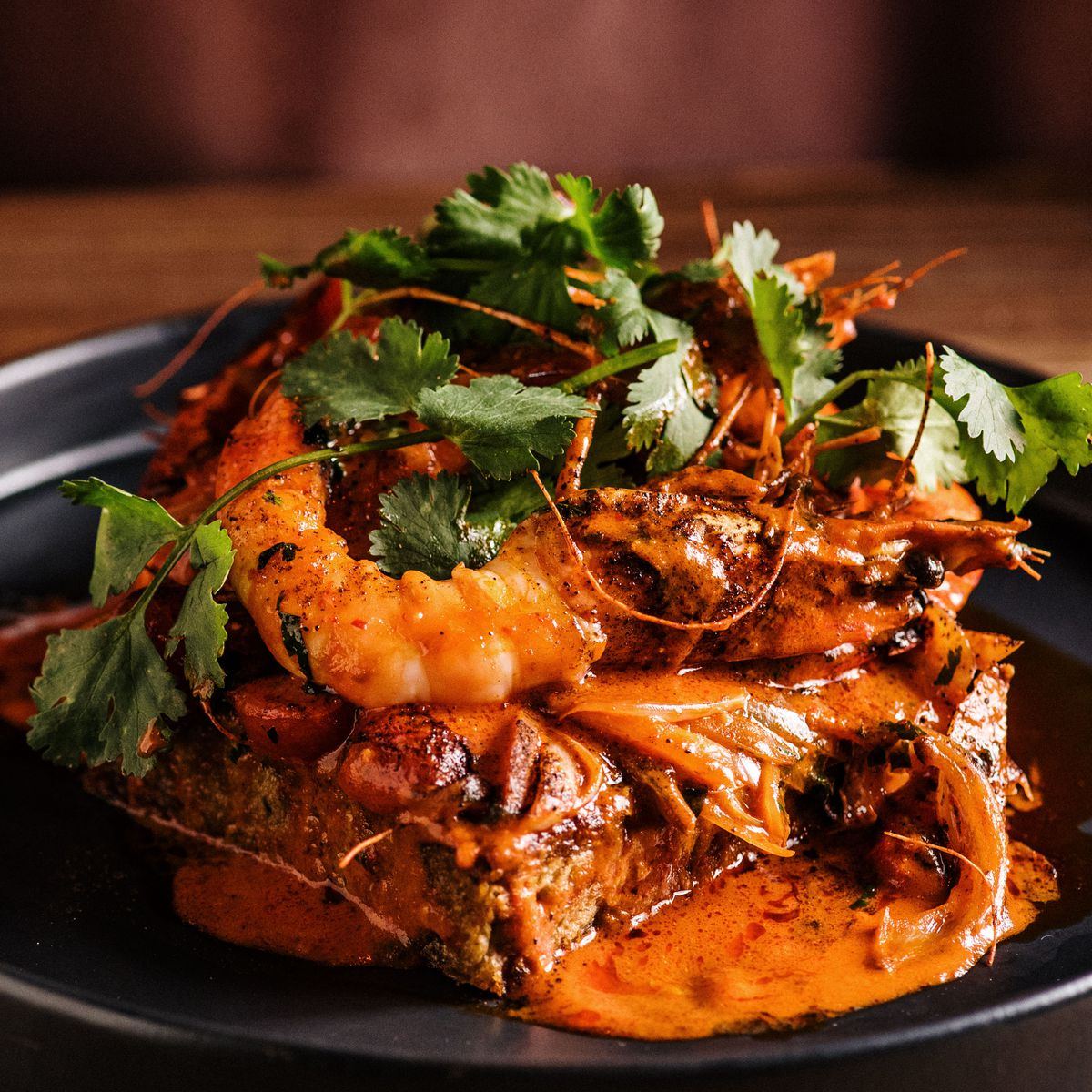 Black bowl of heads-on jumbo shrimp swimming in a spiced red tomato sauce