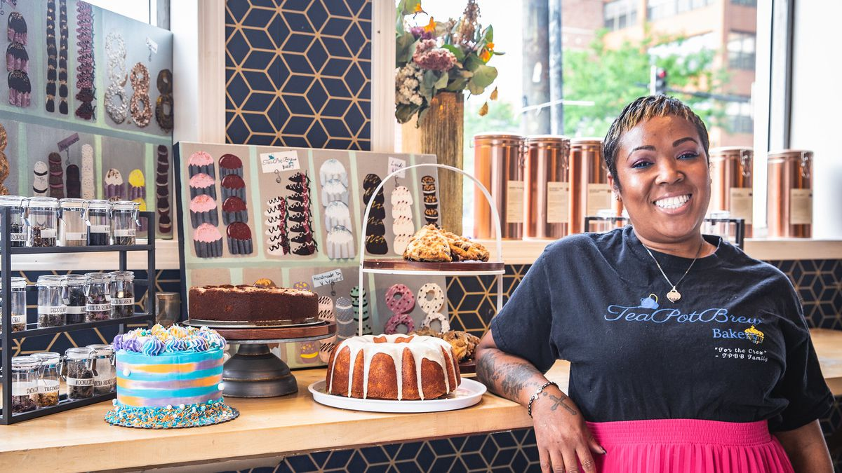 A woman smiling next to a counter with cakes and desserts.