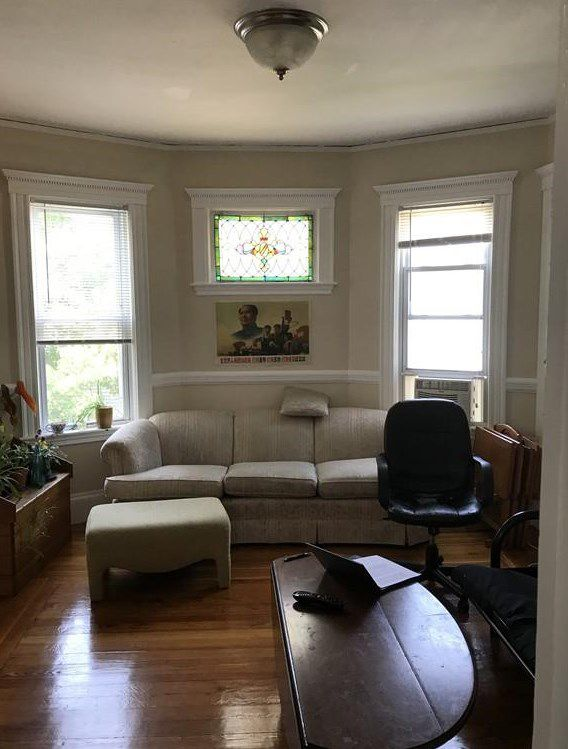 A small living room with a couch against a bay window.