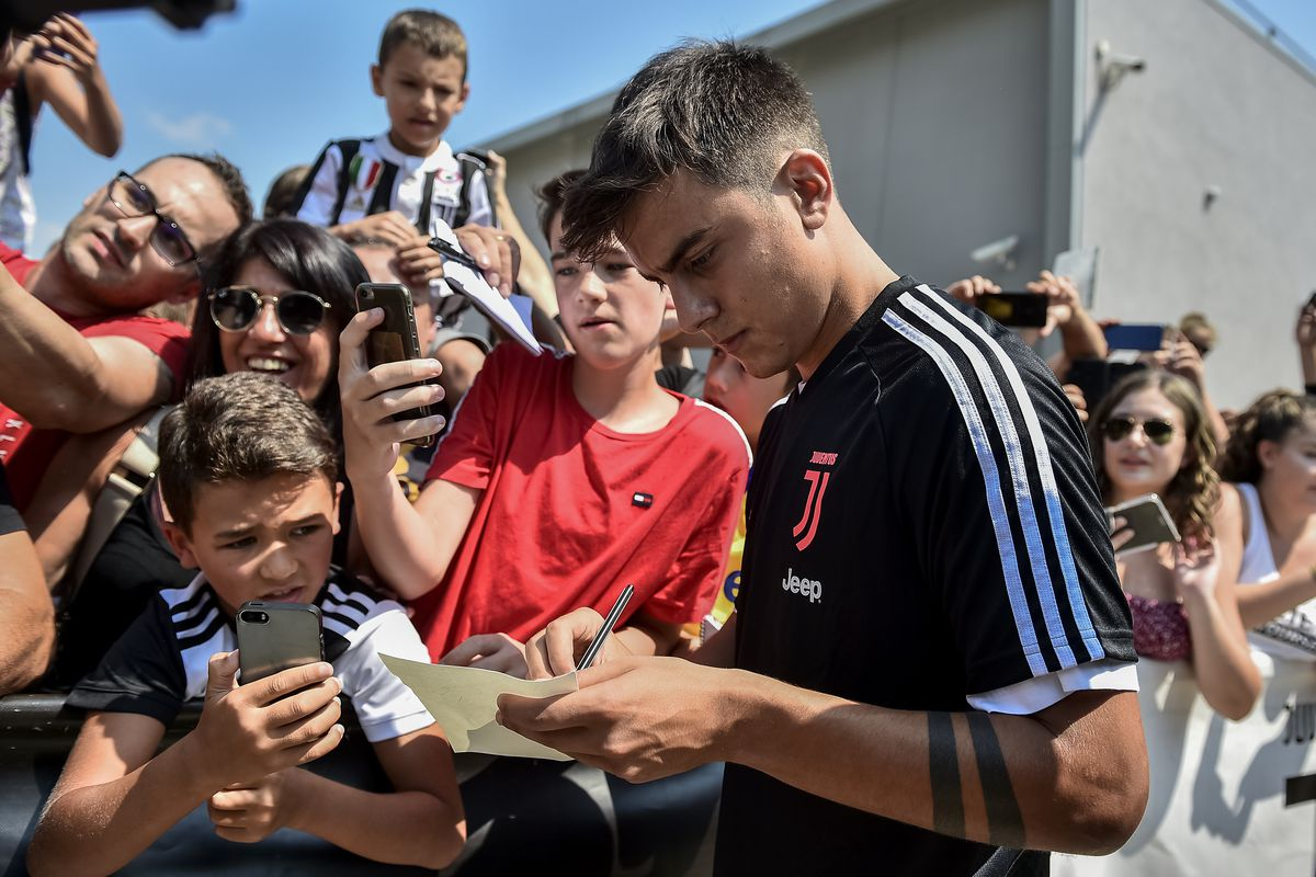 Paulo Dybala of Juventus FC signs an autograph for a fan...