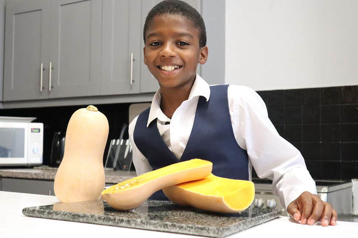 Omari McQueen poses in his kitchen