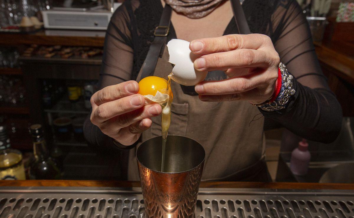 Hands cracking an egg yolk.