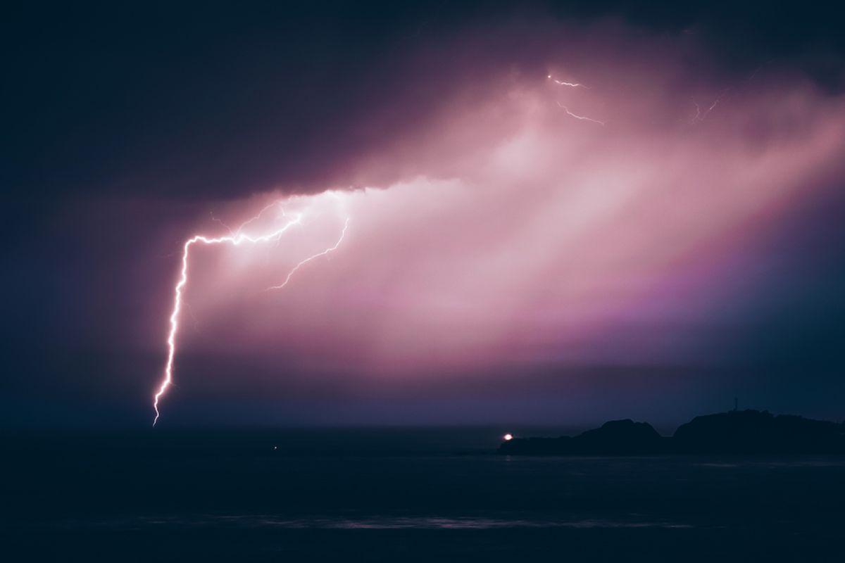 A bolt of purplish lightning in the sky.