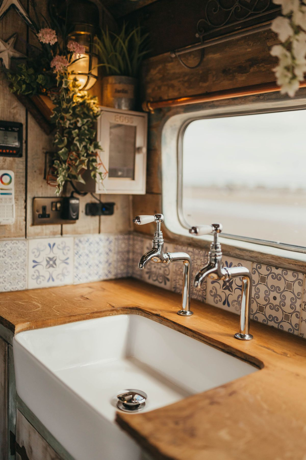 A close-up of the camper's white farmhouse sink, with wood countertops and silver faucets. There's also a blue-and-white backsplash and a large window above the sink.