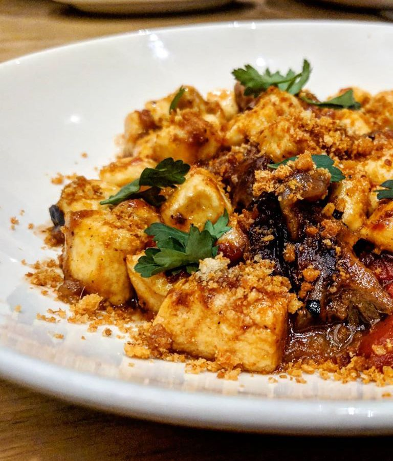 A gnocchi dish topped with lamb, breadcrumbs, sauce, and parsley sits on a white plate on a light wooden table