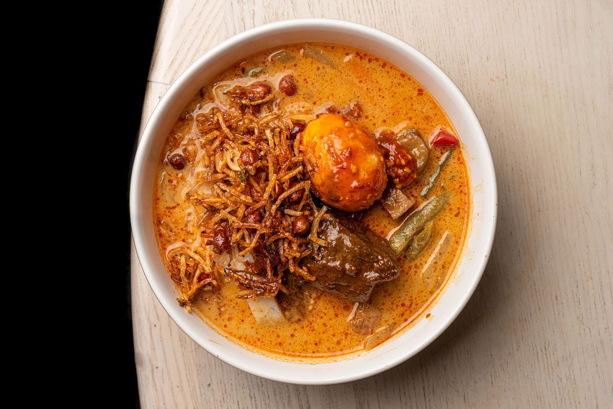A bowl of curry soup with a spicy boiled egg.