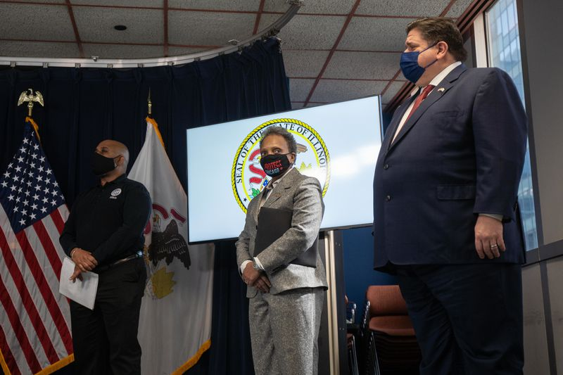 Mayor Lori Lightfoot, center, and Gov. J.B. Pritzker, right, listen during a news conference at the Thompson Center in February.