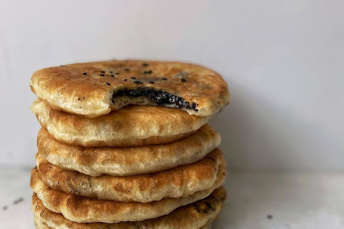 Browned pancakes are stacked on top of each other. A bite out of the top one reveals a black sesame filling.