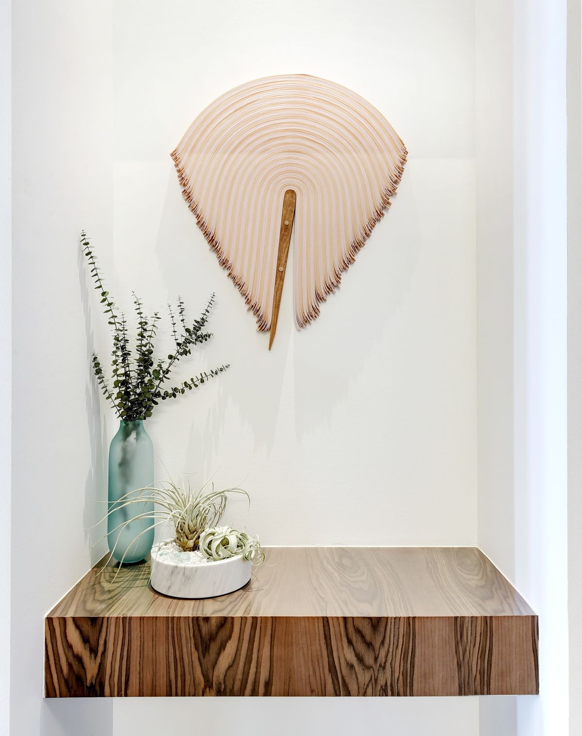 A pink and brown fabric sculpture curved in a fan shape in a niche above a small wooden table.
