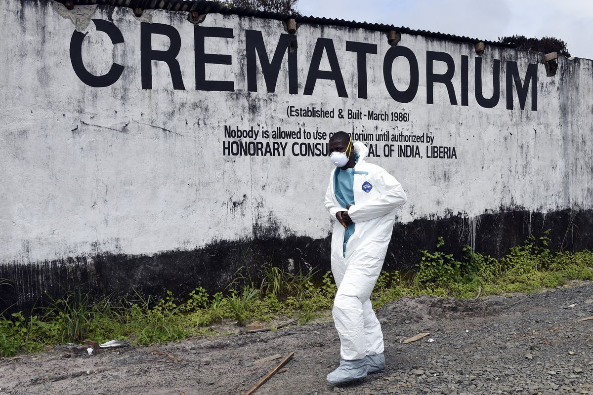 A medical staff member wearing a protective suit walks past the crematorium where victims of Ebola are burned, in Monrovia, Liberia.