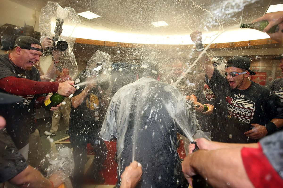 Putz (L) and Parra spray champagne on Derrick Hall after clinching the NL West in 2011