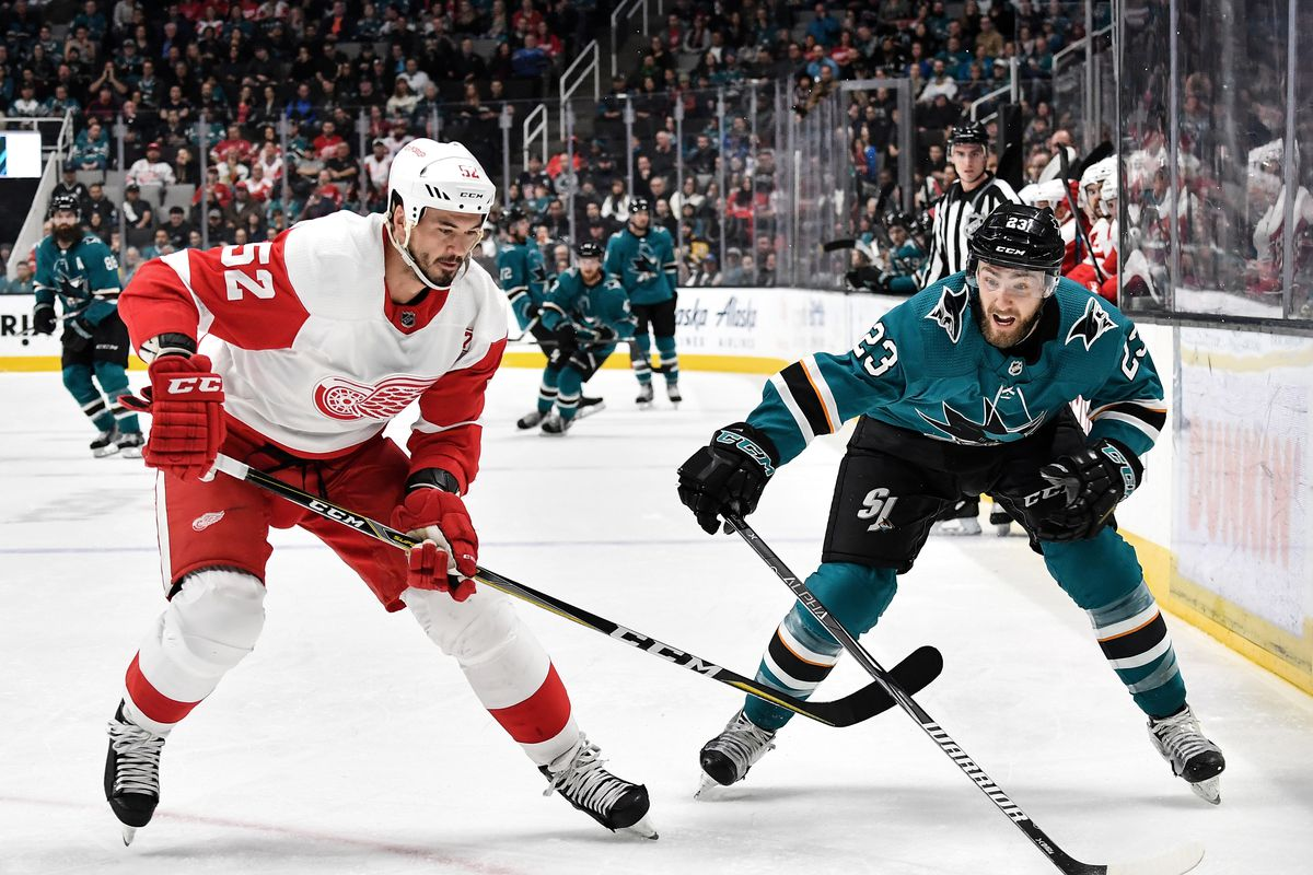 SAN JOSE, CA - MARCH 25: Barclay Goodrow #23 of the San Jose Sharks fights for the puck against Jonathan Ericsson #52 of the Detroit Red Wings at SAP Center on March 25, 2019 in San Jose, California