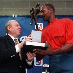 Jazz star Karl Malone looks at the NBA's MVP trophy that was presented to him by Larry H. Miller at a press conference inside the Delta Center on May 18, 1997.