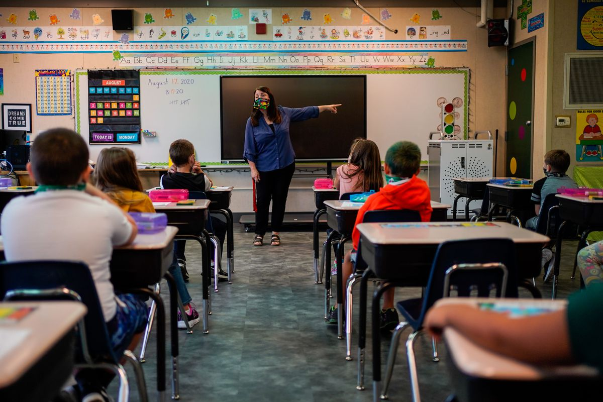 A teacher wearing a mask stands in front of a blackboard as second grade students sit at desks and listen.