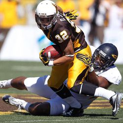 Wyoming running back DJ May is pulled down by Toledo during an NCAA college football game in Laramie, Wyo., Saturday, Sept. 8, 2012.