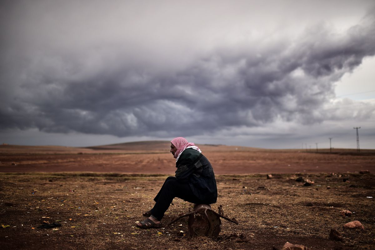 A Kurdish man sits across the border from Kobane, a town ISIS laid siege to.