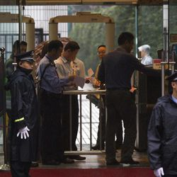 A man places his bag for security check while officials prepare the attendees' name list at a security check point of the Intermediate People's Court in Chengdu, where Wang Lijun stands for his verdict trial in southwest China's Sichuan province Monday, Sept. 24, 2012. The Chinese court sentenced the former police who exposed a murder by a Chinese politician's wife to 15 years in prison Monday in a decision that sets the stage for China's leadership to wrap up a seamy political scandal and move ahead with a generational handover of power.