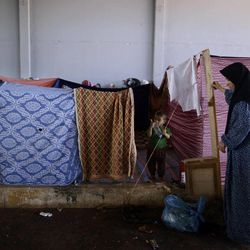 In this Thursday, Sept. 13, 2012, photo, a Syrian woman, who fled her home due to government shelling,  constructs a makeshift tent made of sheets, as she and her family take refuge at Bab Al-Salameh crossing border, hoping to cross to one of the refugee camps in Turkey, near the Syrian town of Azaz. The days are still hot across the fertile plains of northern Syria, but at night there is a hint of a chill an ominous harbinger of winter's approach and the deepening of the humanitarian crisis gripping a country wracked by civil war.