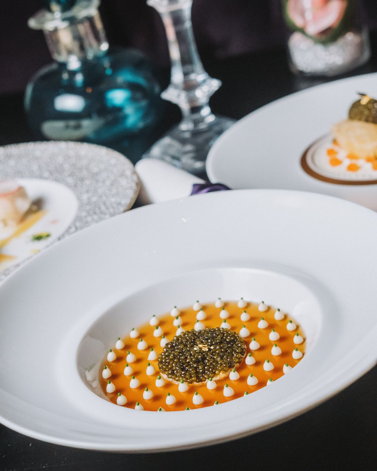 Osetra caviar served atop king crab in a crustacean gelée dotted with cauliflower puree