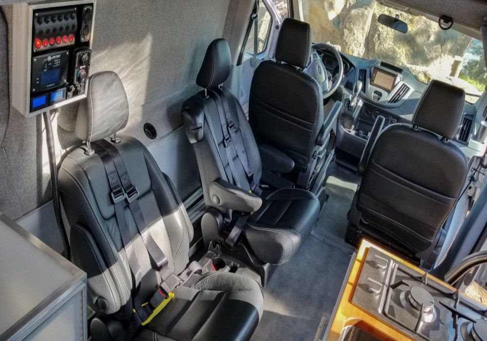 The interior of a RV camper van. There are four seats. Two of the seats are across from a kitchenette with a stove.