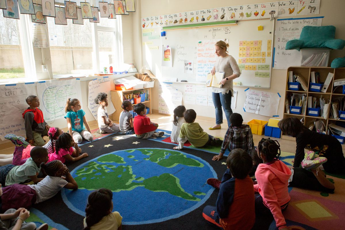 A group of children sit on a rug with a drawing of the Earth on it as their teacher, wearing a white sweater and blue jeans, conducts a lesson in front of a white board.