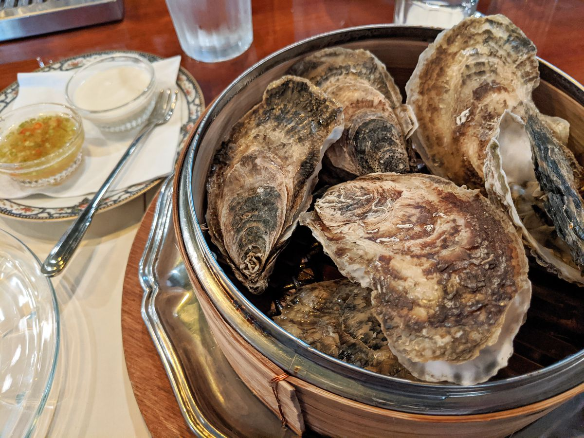 A wooden basket with a metallic insert that contains oval shaped oysters in their shell. In the distance a white plate sits with two small bowls with a white sauce and a yellow one.